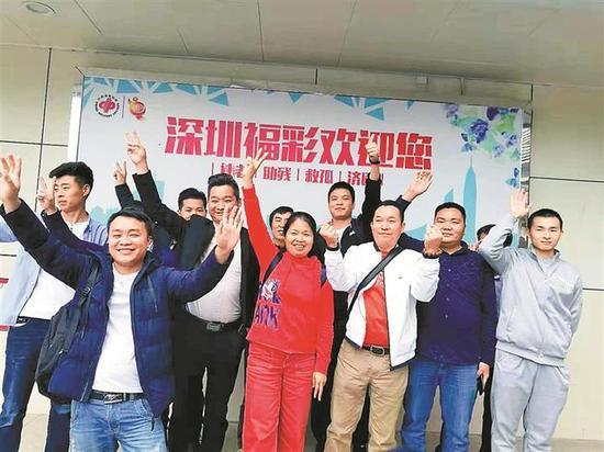 深圳28人合买团双色球中奖代表和销售员在深圳福彩兑奖大厅门口露脸合影留念。