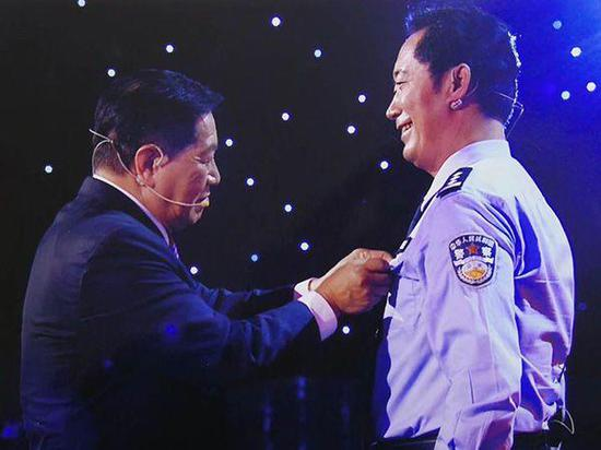 在央视《挑战不可能》的节目录制现场,国际刑侦鉴识专家李昌钰将一枚印有他名字的警徽戴在林宇辉胸前。 受访者 供图