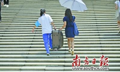 中山市内高校,报到的新生提着行李走向宿舍。