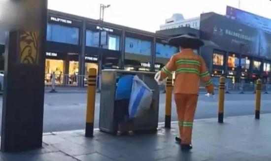 女孩将头伸进垃圾桶找东西▲