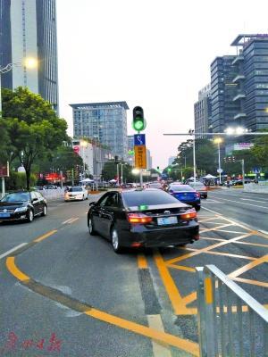 """""""借道左转""""车道绿灯亮了,一辆车驶入规定车道内。"""