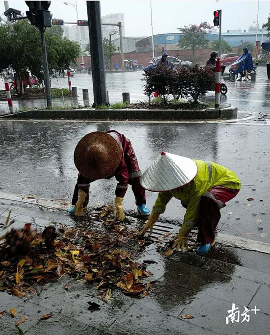 防汛人员在城市道路上排查疏通下水管道。
