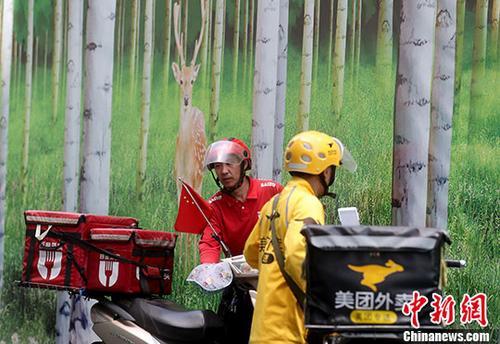 资料图:北京西单街头的外卖骑手准备送餐。中新社记者 张宇 摄