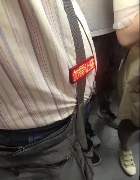 老人挂勿需让座提示牌乘地铁:让城市文明更可亲