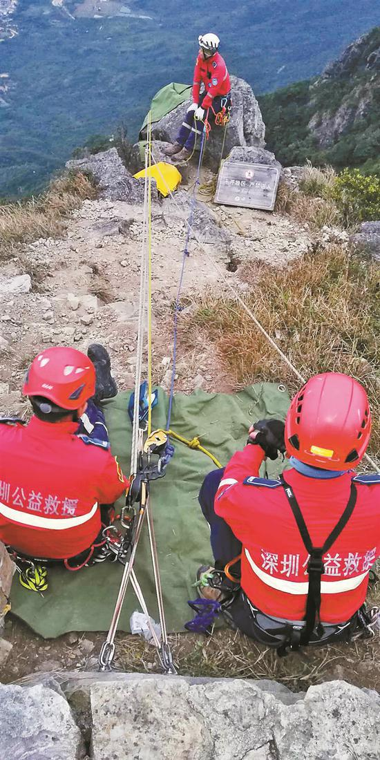 救援队员在山顶建立保护站。