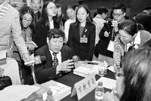 市人大代表蒋厚全在教育局摊位咨询。