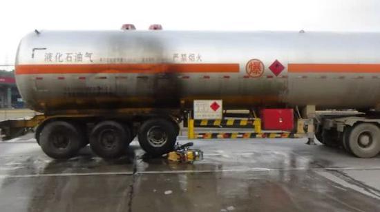 现场被扑灭的摩托车和液化石油气气罐车
