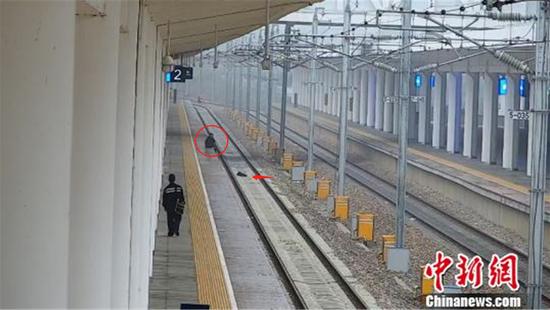 该男子将背包扔入铁轨并坐在站台边缘。警方监控视频截图