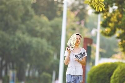 昨日下午,市民拿着扇子挡着脸在阳光下跑步。广州日报全媒体记者陈忧子 摄