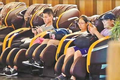 一家商场里,一些市民坐在按摩椅上看手机。广州日报全媒体记者莫伟浓 摄