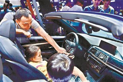一位父亲在给孩子讲解车内的按钮。广州日报全媒体记者王燕 摄