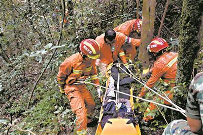 """""""救援小组""""利用绳索挂钩将被困者抬到山下。"""