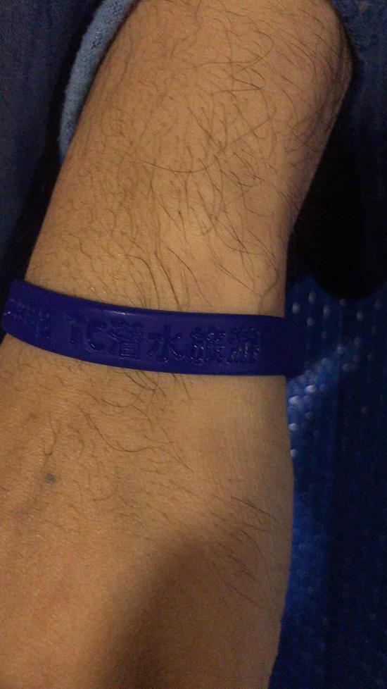 """不幸遇难的中年男性,手上带有一根写有""""潜水旅游""""字样的深蓝色塑胶类手环。普吉泰中旅游协会会长郑伟 供图"""