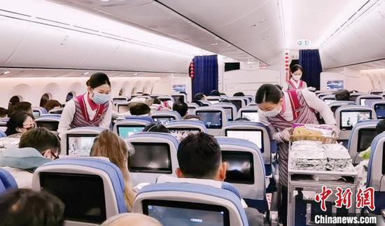 资料图:南航空乘在飞机上提供服务。南方航空供图