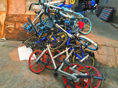在江门城郊某市场附近的窄巷内,共享单车被堆成一堆