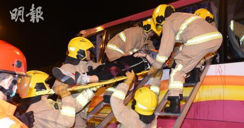 消防员正对旅游巴士内的伤者实施救援。图片来源:香港《明报》/蔡方山 摄