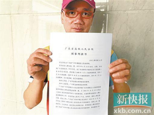 ■谭志坚手持广东省高院的无罪判决书。 新快报记者 何生廷/摄