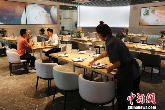 工作人员正在布置共享餐厅座位区。 殷立勤 摄