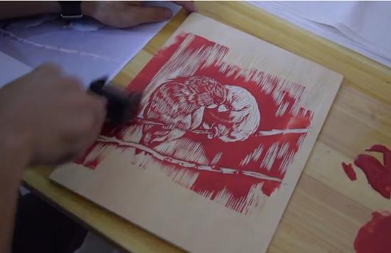 陈博在进行版画制作的上油墨环节