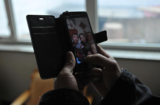 2月3日,农历腊月二十九。李玉宝的手机里存着一张全家福。今年春节,儿子带着妻儿去东北老丈人家过年,家里就剩下李玉宝老两口。 新京报记者 吴江 摄