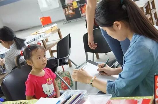 陳小如在为一个小女孩手绘肖像