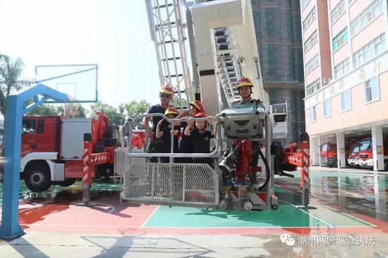 消防官兵向孩子们介绍消防车辆和配备器材的名称、用途和使用方法。