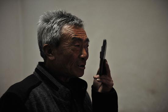 2月5日,农历正月初一凌晨零点刚过。李玉宝接到了儿子从东北发来的拜年问候。 新京报记者 吴江 摄