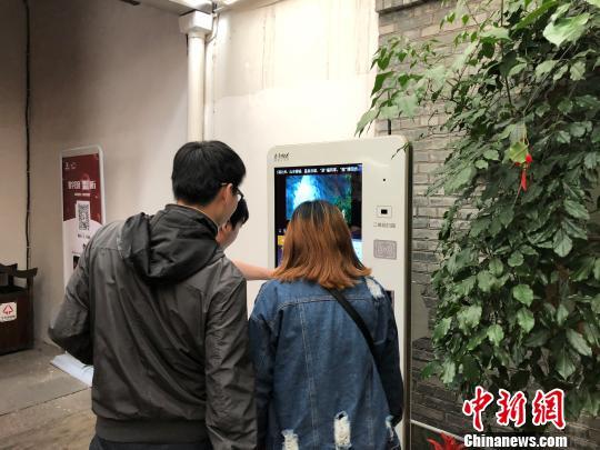"""图为在福州三坊七巷景区的游客中心内,几名游客正通过大屏""""点读机"""",了解三坊七巷的概况。 闫旭 摄"""