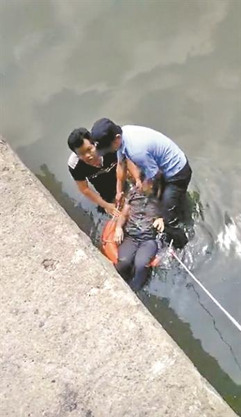 众人合力将其中一名落水者救上岸