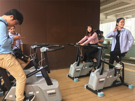 市民在健身单车上踩动即可蓄电给手机充电