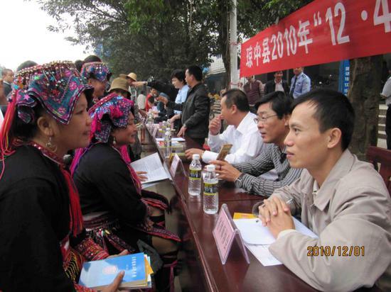 2010年12月1日,郑穗军(右一)和其他志愿律师在海南省琼中县街头接受少数民族群众咨询