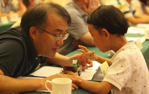 8月20日,首届全球华人青少年社会创新大赛成果分享会在北京成功举办,复赛晋级的小小社创客们对自己方案阶段性的成果进行了展示。图为评委在和参赛选手交流