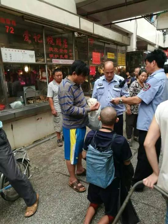 图为广州黄浦区某菜市场,古先生报警后,当地警方来到现场调查情况,左侧穿横条衣服男子疑似为彭小六的控制者