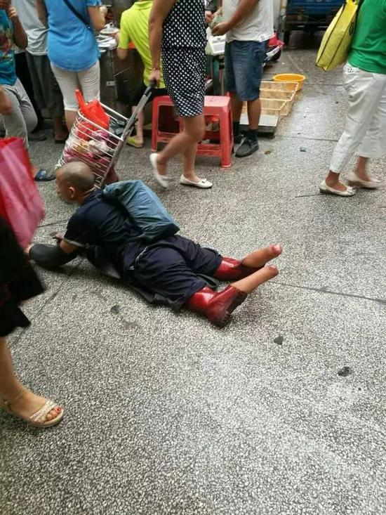 图为广州黄浦区某菜市场,被截双腿的彭小六正在行乞