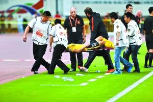 替补上场的左后卫陈泽鹏受伤被担架抬下场,一旁的斯科拉里有些无奈。 特派记者 廖艺 摄