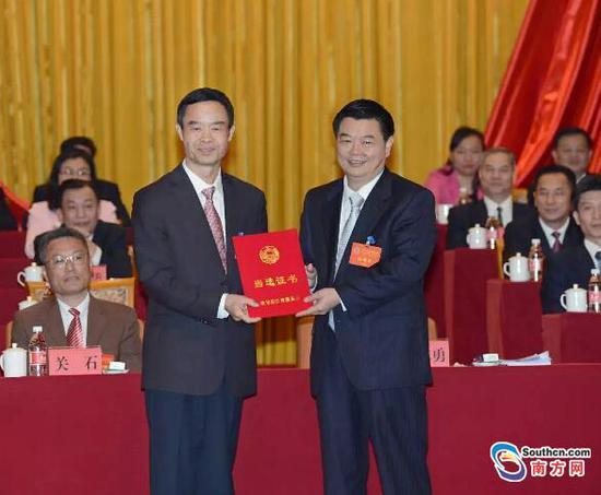 阳江市委书记陈小山向新当选的阳江市政协主席丘志勇颁发当选证书。
