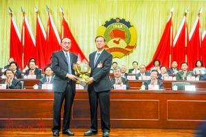 新一届市政协主席熊志翔(前左)向上一届市政协主席杨晓光送上一束鲜花。