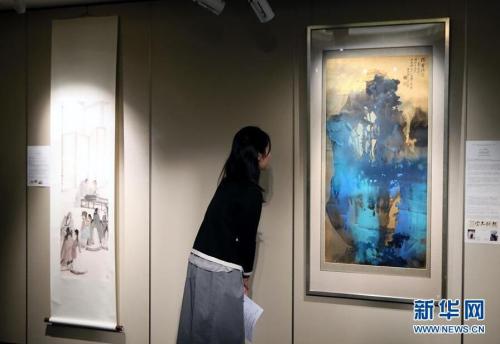 3月14日,一位记者在香港苏富比春拍记者会上观看张大千的泼墨泼彩山水画作《灊霍瑞霭》。香港苏富比将于4月4日举行中国书画专场拍卖会,呈献逾300幅中国近现代书画佳作,总估值约1.6亿港币。 新华社记者 李鹏 摄