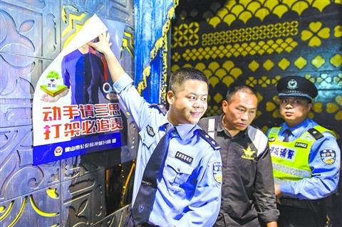 """昨日,在禅城区创意产业园格莱美汇内,禅城公安民警在显著位置张贴""""劝架""""海报。  /佛山日报记者王澍摄"""