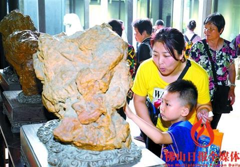 一位市民带小朋友在梁园参观石展。/佛山日报记者甘建华摄