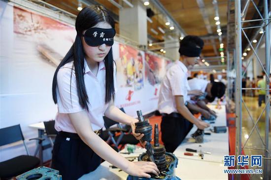 """7月14日,技工院校学生在演示""""盲装变速箱""""。新华社记者王建威 摄"""