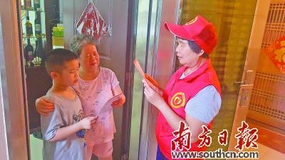 志愿楼长入户宣传文明城市创建工作。                     朱峰 摄