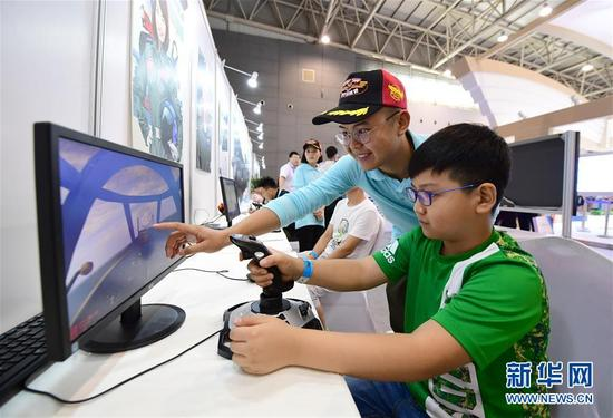 8月24日,小朋友在工作人员的指导下体验一款模拟飞行游戏。 新华社记者 邵瑞 摄