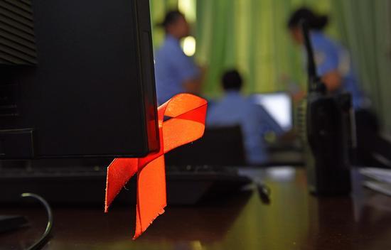 一缕斜阳透过艾滋病专管区警察办公室的窗户,照在艾滋病红丝带上。
