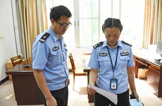 专管大队的副大队长何淑玲(右)向所医院院长刘祺了解艾滋病学员的病情。