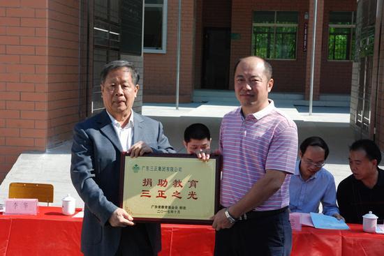 广东省教育基金会秘书长许怀升先生向广东三正集团形象管理部总经理李华先生回赠牌匾