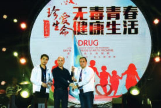 舞台上,粤X乐队成员代表从龙江镇党委副书记、镇禁毒办主任何碧耀手中接过禁毒宣传的大旗,粤X乐队正式成为龙江禁毒的宣传大使。