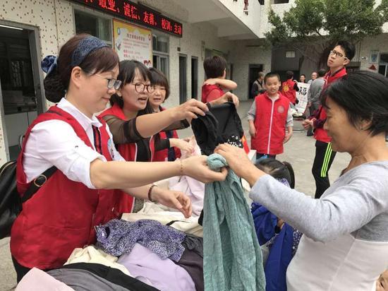 义工们向凤兰小学学生家长发放爱心物资。