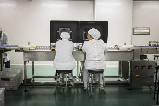 广药集团白云山制药厂生产线上,员工正在进行成品检查