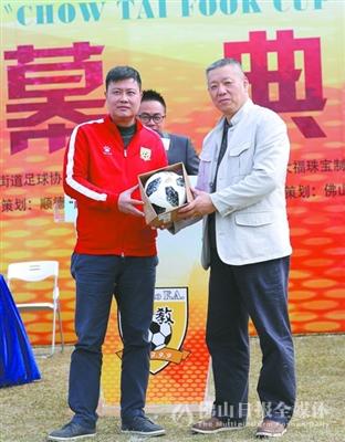 伦教足协会长薛国康(左)向周大福公司代表张振宇赠送纪念足球。